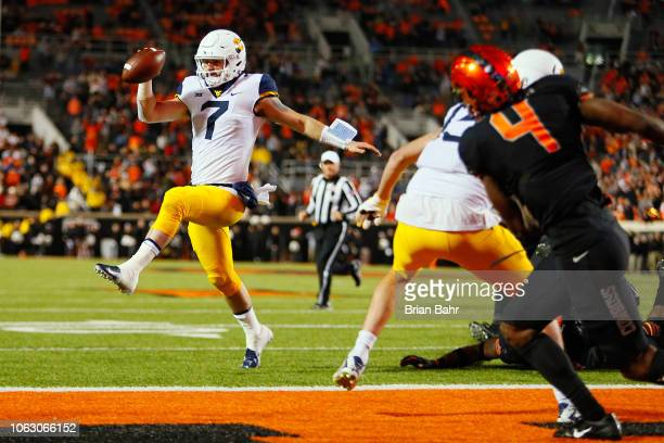 Quarterback Will Grier of the West Virginia Mountaineers leaps into the end zone for a touchdown against the Oklahoma State Cowboys in the fourth...