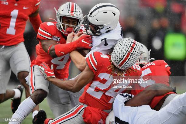 Quarterback Will Levis of the Penn State Nittany Lions is dragged down by Jordan Fuller Shaun Wade and Baron Browning all of the Ohio State Buckeyes...
