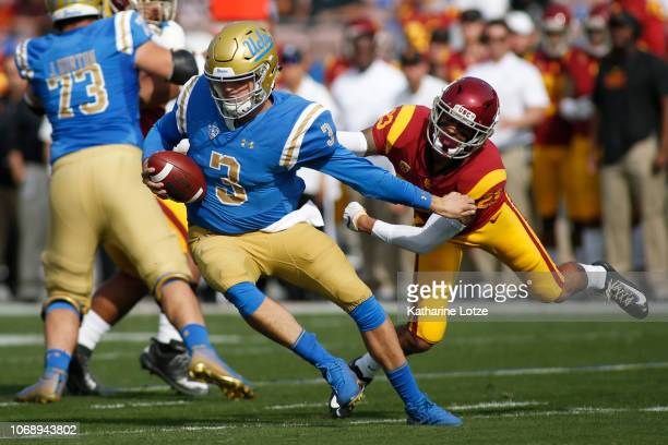 Quarterback Wilton Speight of the UCLA Bruins tries to break free from a tackle by cornerback Jonathan Lockett of the USC Trojans during the first...