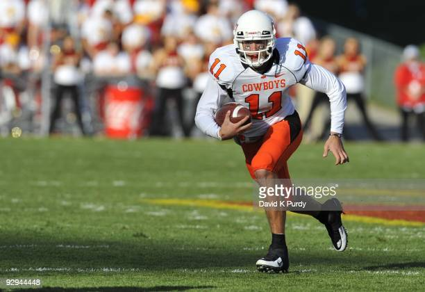 Quarterback Zac Robinson of the Oklahoma State Cowboys scrambles for yards in the first half of play during the game against the Iowa State Cyclones...