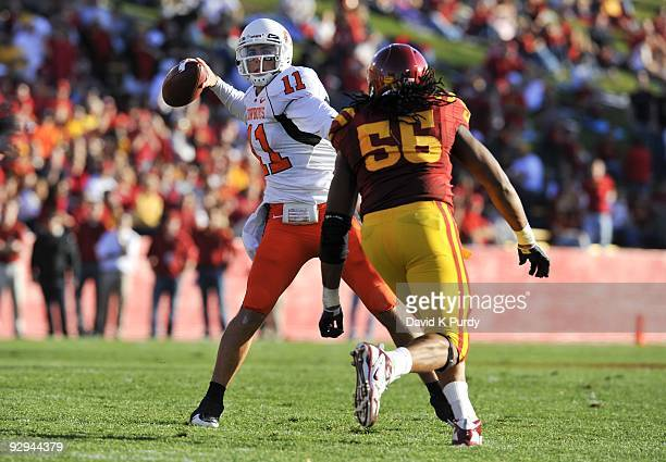 Quarterback Zac Robinson of the Oklahoma State Cowboys throws under pressure from defensive end Christopher Lyle of the Iowa State Cyclones in the...