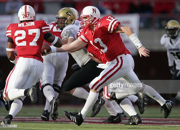 Quarterback Zac Taylor of the Nebraska Cornhuskers hands off the ball to Kenny Wilson during the game against the Colorado Buffaloes on November 24...