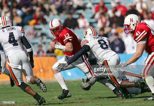 Quarterback Zac Taylor of the Nebraska Cornhuskers runs to avoid the sack by Jerraud Powers of the Auburn Tigers during the ATT Cotton Bowl Classic...