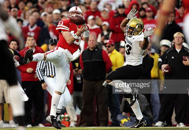 Quarterback Zac Taylor of the Nebraska Cornhuskers tries to catch a pass as defensive end Abraham Wright of the Colorado Buffaloes defends in the...