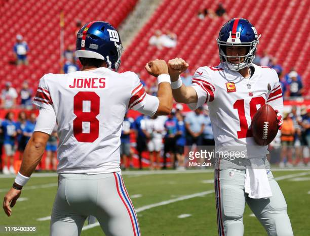 Quarterbacks Daniel Jones and Eli Manning of the New York Giants fist bump during warmups before the game against the Tampa Bay Buccaneers at Raymond...