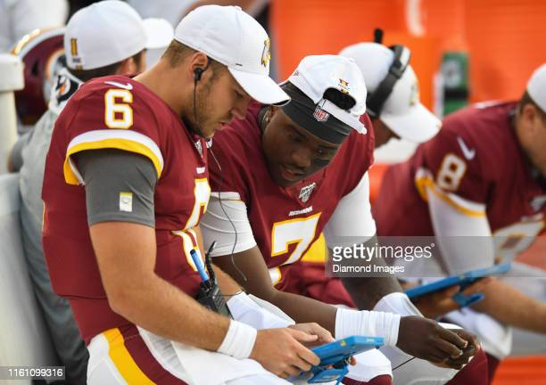 Quarterbacks Josh Woodrum and Dwayne Haskins of the Washington Redskins review plays on an iPad in the first quarter of a preseason game against the...