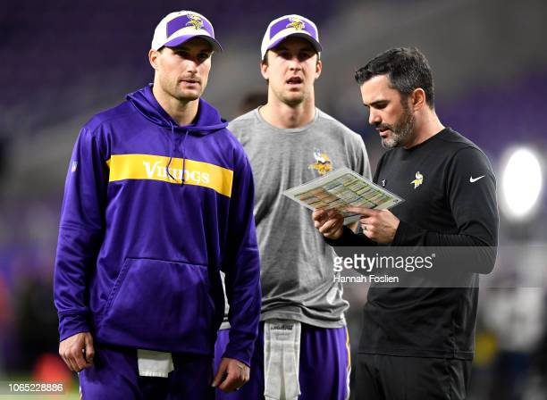 Quarterbacks Kirk Cousins and Trevor Siemian of the Minnesota Vikings and quarterbacks coach Kevin Stefanski talk on field before the game against...