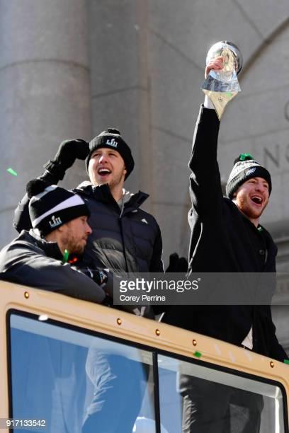 Quarterbacks Nick Foles Nate Sudfeld and Carson Wentz of the Philadelphia Eagles acknowledge fans as Wentz hoists the Vince Lombardi Trophy atop a...