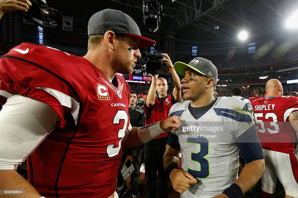 Quarterbacks Russell Wilson #3 of the Seattle Seahawks and Carson Palmer #3 of the Arizona Cardinals talk on the field following the NFL game at the University of Phoenix Stadium on January 3, 2016 in Glendale, Arizona. The Seahawks defeated the Cardinals 36-6.