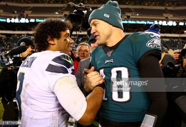 Quarterbacks Russell Wilson of the Seattle Seahawks and Josh McCown of the Philadelphia Eagles shake hands after the Seahawks win the NFC Wild Card...