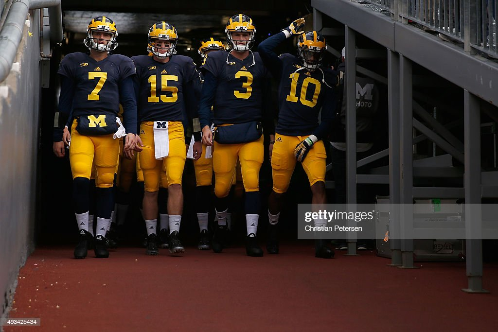 Quarterbacks Shane Morris #7, Jake Rudock #15, Wilton Speight and Zach Gentry #10 of the Michigan Wolverines of the Michigan Wolverines take the field for warm ups to the college football game against the Michigan State Spartans at Michigan Stadium on October 17, 2015 in Ann Arbor, Michigan.