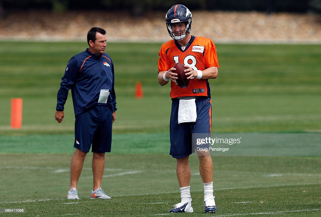 Quarterbacl Petyon Manning prepares to deliver a pass as head coach Gary Kubiak looks on during a joint training session with the San Francisco 49ers and the Denver Broncos at the Denver Broncos Training Facility on August 27, 2015 in Englewood, Colorado.