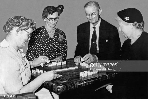A quartet of members of a senior citizens group plays dominos at the YWCA which sponsors the gatherings Oklahoma City Oklahoma April 1954