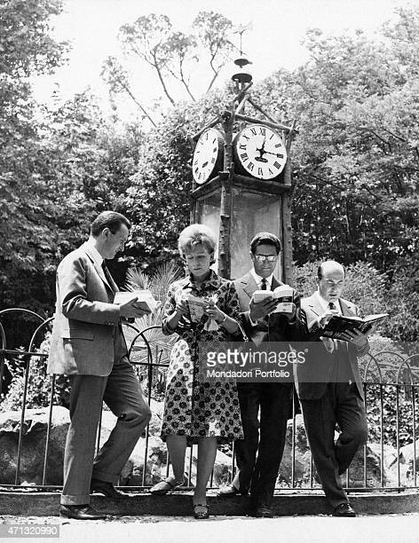 Quartetto Cetra reading something in front of a street clock The Italian vocal band is formed by the singer Lucia Mannucci the singer and drummer...