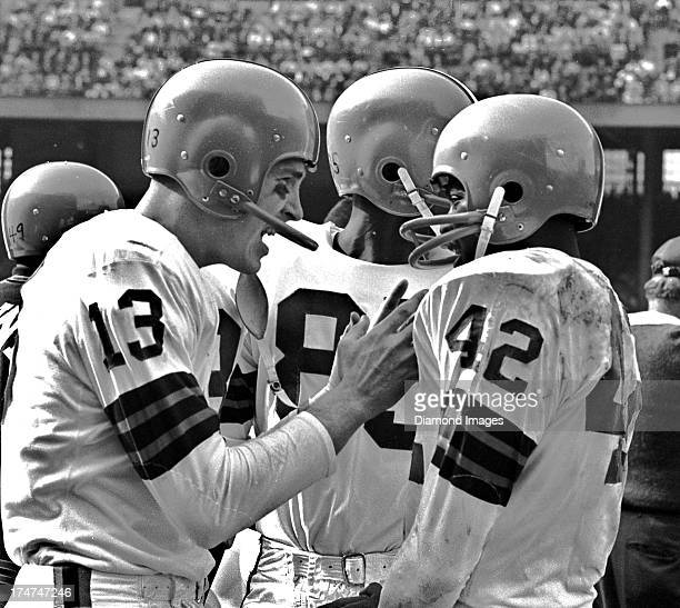 Quaterback Frank Ryan of the Cleveland Browns talks with wide receiver Paul Warfield on the sideline during a game circa 1964 at Cleveland Municipal...