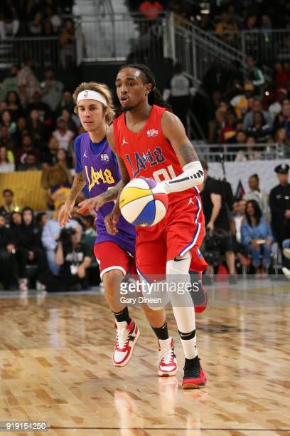 Quavo dribbles the ball while guarded by Justin Bieber during the NBA AllStar Celebrity Game presented by Ruffles as a part of 2018 NBA AllStar...