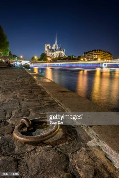 quayside of seine river with notre-dame cathedral and boat light trails on the water at sunset in paris, france. - quayside stock pictures, royalty-free photos & images