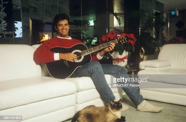 Québec Canada 20 janvier 1991 Le chanteur Roch VOISINE chez lui près de Montréal Ici jouant de la guitare assis dans le canapé de son salon sa chatte...