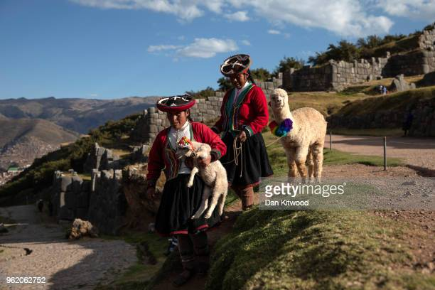 Quechua women walk through the Inca ruins of Sacsayhuaman looking to pose for photographs in exchange for money on May 23, 2018 in Cusco, Peru. At...