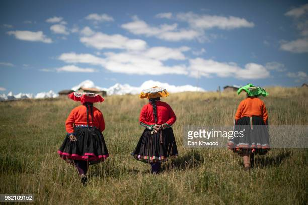 Quechua women walk towards their homes under Mount Ausangate on May 23, 2018 in Tinki, Peru. Many Quechua families, especially women in high altitude...