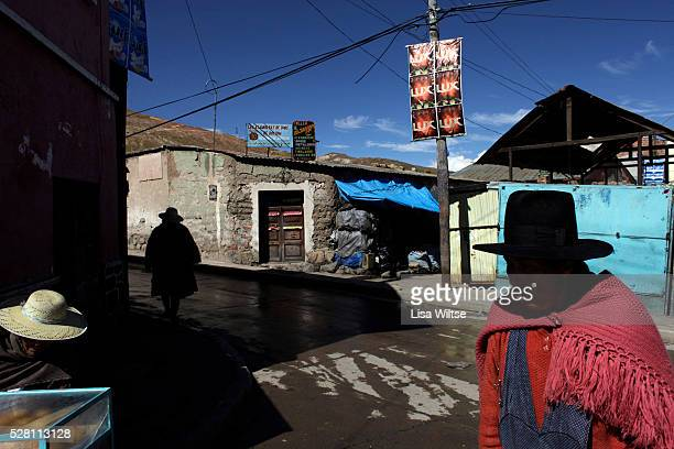 Quechuan women at the miner's market in the early morning prepare to sell grain alcohol, food and coca leaves to the miners on their way to work....