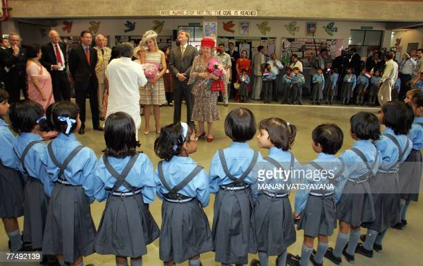 Queen Beatrix of The Netherlands is watched by a group of schoolchildren as she arrives for a visit to NGO-based school Deepalaya in New Delhi, 25...