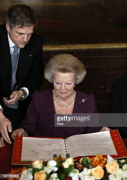 Queen Beatrix of the Netherlands looks over the Act of Abdication during a ceremony in the Moseszaal at the Royal Palace on April 30 2013 in...