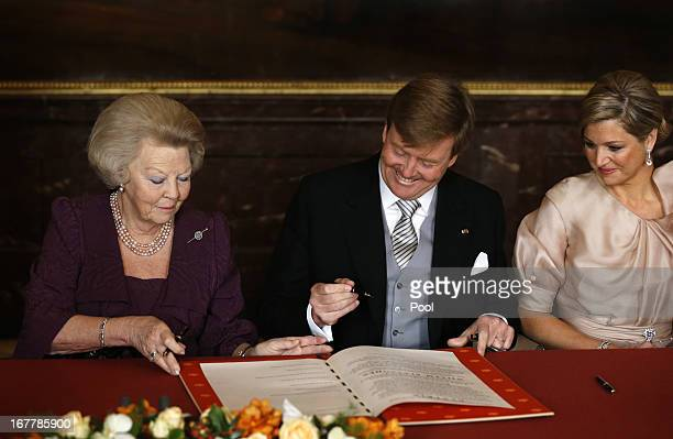 Queen Beatrix of the Netherlands passes the Act of Abdication to her son Prince WillemAlexander of the Netherlands to sign as his wife Princess...