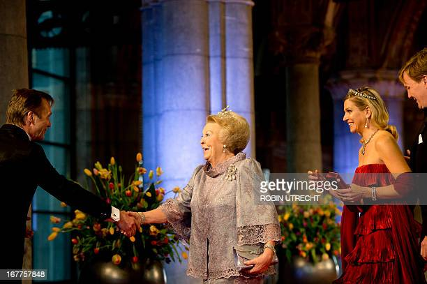 Queen Beatrix of the Netherlands shakes hands on April 29 2013 with an official as she arrives with son Prince WillemAlexander and his wife Princess...