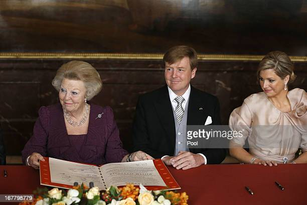 Queen Beatrix of the Netherlands signs the Act of Abdication as her son Prince WillemAlexander of the Netherlands and his wife Princess Maxima of the...