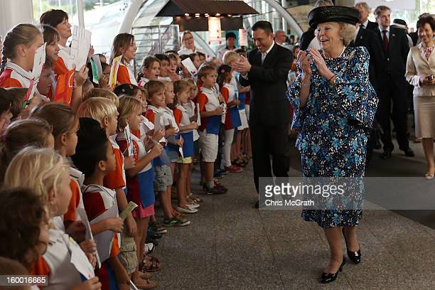 Queen Beatrix of the Netherlands sings along with dutch students from the Hollandse School after touring the Singapore A*Star Fusionworld on January...