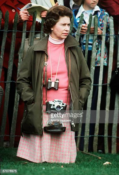 Queen Elizaberh ll a keen photographer kneels down and watches the Badminton Horse Trials on October 14 1975 in England