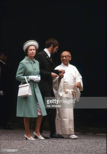 Queen Elizabeth accompanied by Shinto priest visits the Ise Grand Shrine, a Shinto temple, during her royal tour of Japan in 1975