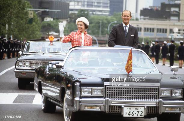 Queen Elizabeth and Prince Philip drive through Tokyo streets in open limousine during Royal Tour of Japan in May 1975