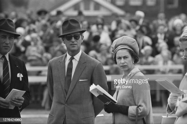 Queen Elizabeth and Prince Philip Duke of Edinburgh at the Newbury race meeting in Berkshire UK 20th May 1966 On the far left is the Queen's racing...