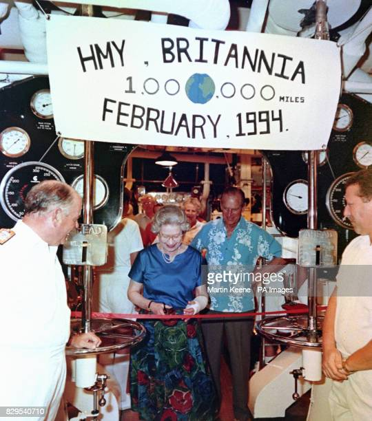 Queen Elizabeth cuts a ribbon in the engine of the Royal Yacht Britannia watched by the Duke of Edinburgh and Admiral bob Woodward L to mark the...