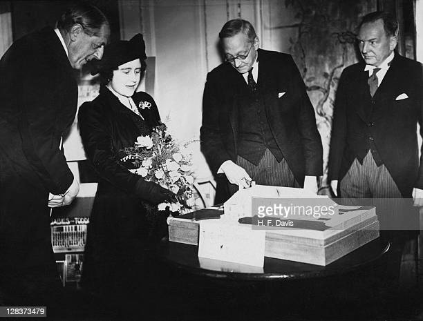 Queen Elizabeth examines a model of the Countess of Strathmore Homes during a visit to the Waifs Strays Bazaar at the Dorchester Hotel London 5th...