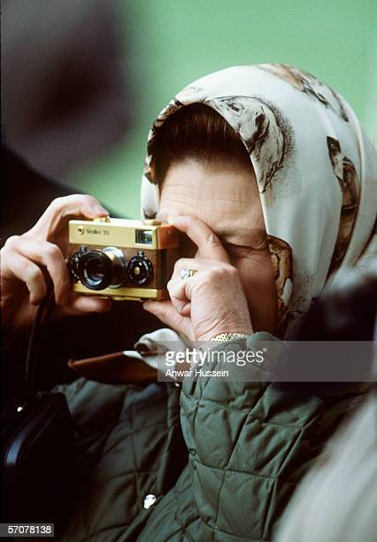 Queen Elizabeth II, a keen photographer, at Windsor Horse Show with her gold Rollei 35 camera in 1978 in England.