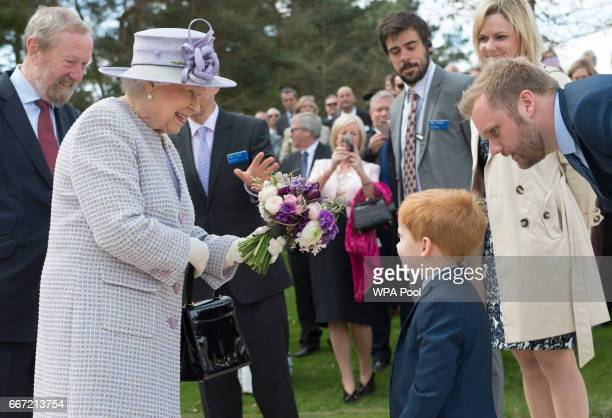 Queen Elizabeth II accepts a bouquet from Arthur Craft who's father works at the Zoo as she arrives to open the new Centre for Elephant Care at ZSL...