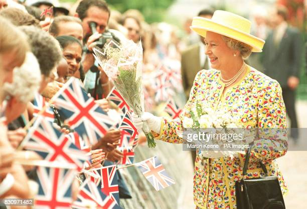 Queen Elizabeth II accepts a bunch of flowers during a walkabout outside Durban City Hall South Africa