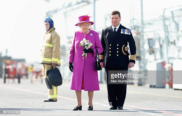 Queen Elizabeth II accompanied by Captain Timothy Henry stands on the flight deck of HMS Ocean before departing by helicopter following a visit to...