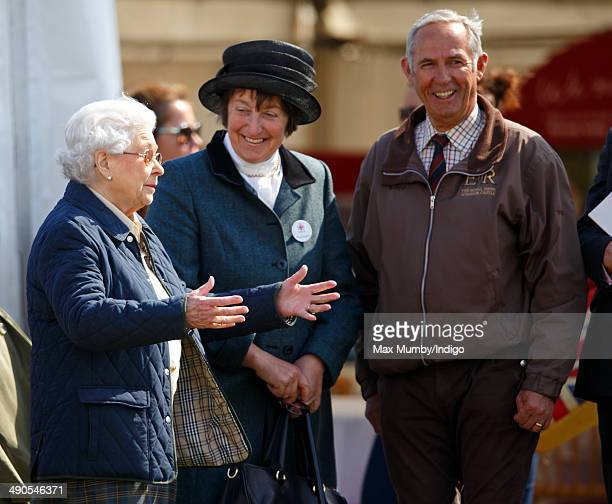 Queen Elizabeth II accompanied by Henrietta Knight and her stud groom Terry Pendry gestures as she watches her horse 'Tower Bridge' compete in the...