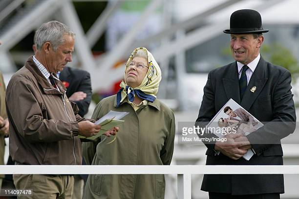 Queen Elizabeth II accompanied by her stud groom Terry Pendry looks up at a passing aircraft as she watches her horse 'St James' compete in the...