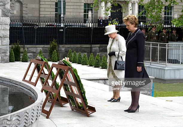 Queen Elizabeth II accompanied by Irish President Mary McAleese lays a wreath at Dublin Memorial Garden on May 17 2011 in Dublin Ireland The Duke and...