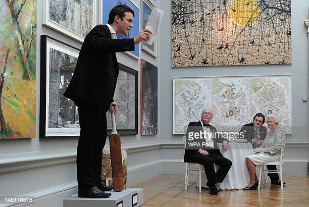Queen Elizabeth II accompanied by Julian Fellowes and an academy director watches a performance as she attends a special 'Celebration of the Arts'...