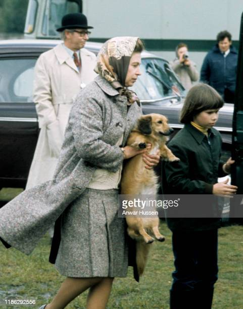 Queen Elizabeth II , accompanied by Lady Sarah Armstrong-Jones, carries one of her pet dogs at Windsor Great Park on May 01, 1977 in Windsor, England.
