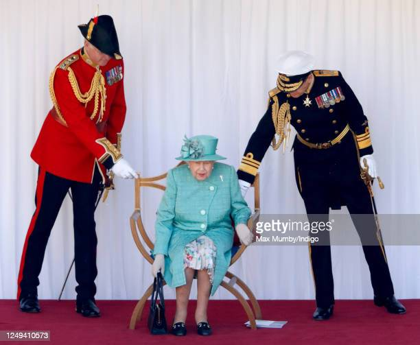 Queen Elizabeth II, accompanied by Lieutenant Colonel Michael Vernon and Vice Admiral Tony Johnstone-Burt , attends a military ceremony in the...