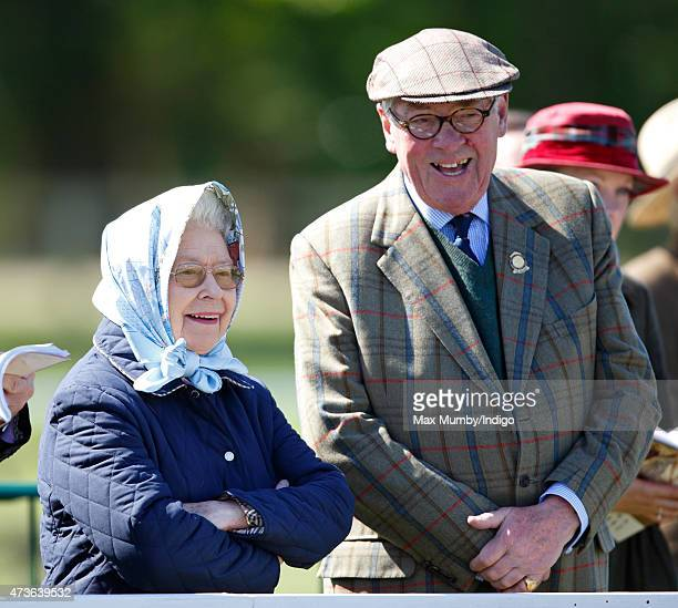 Queen Elizabeth II, accompanied by Lord Vestey, watches her horse 'Balmoral Erica' compete in the Mountain and Moorland Class on day 4 of the Royal...