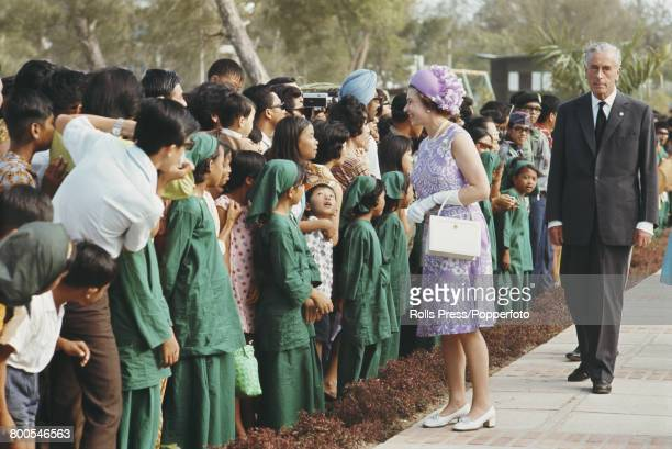 Queen Elizabeth II accompanied by Louis Mountbatten talks with local children and residents during a Commonwealth visit by members of the British...