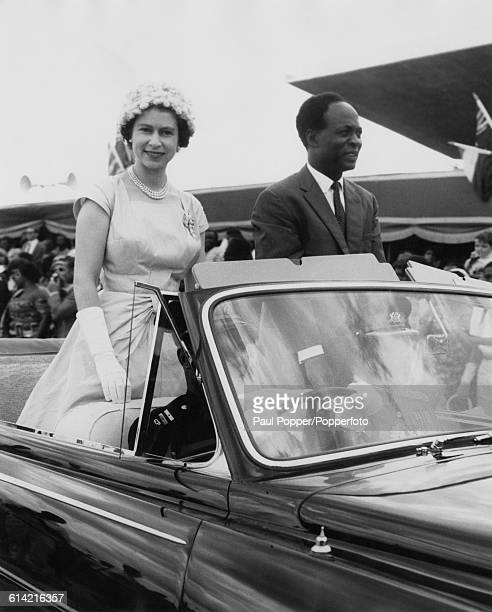 Queen Elizabeth II accompanied by President of Ghana Kwame Nkrumah is driven in an open top car around Kumasi sports stadium for a gathering of...
